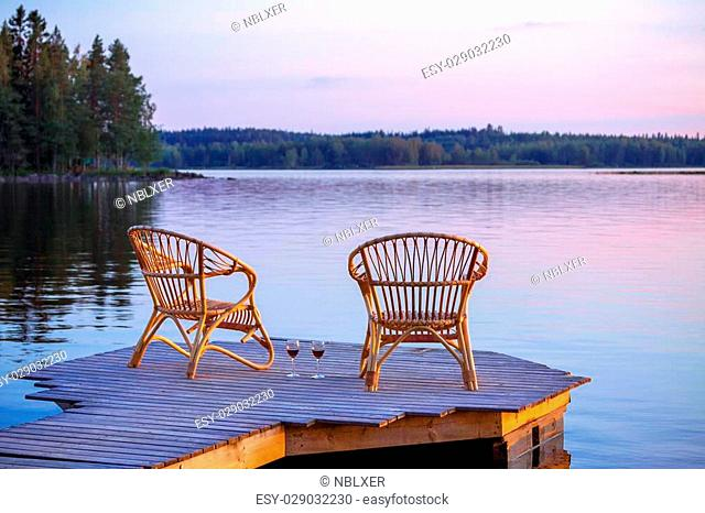 Two chairs on dock with glasses of wine