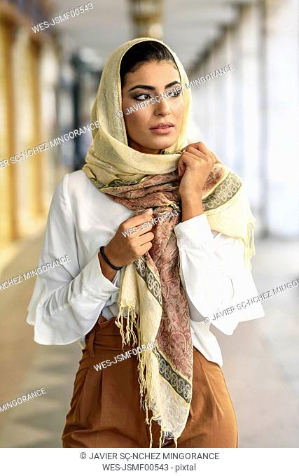 Spain, Granada, young muslim woman wearing hijab in urban city background