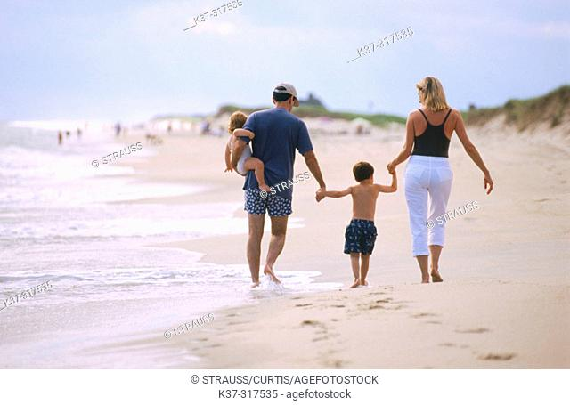 Family on beach. Parents with son and daughter leaving footprints in the sand, nuclear family, Nantucket, Massachusetts , USA