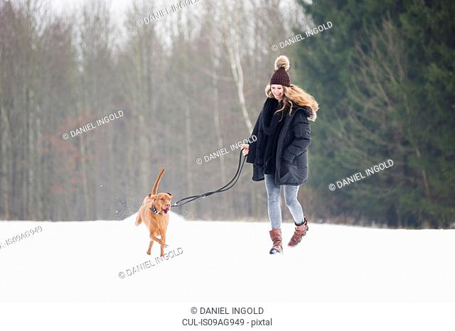 Young woman running with her dog in snowy field