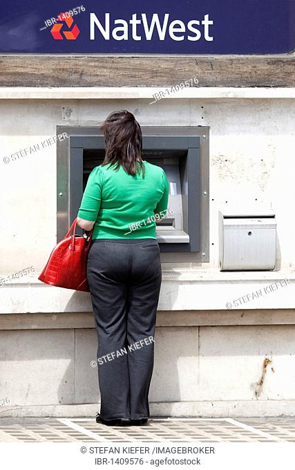 Woman at the cash machine of the NatWest Bank in London, England, United Kingdom, Europe