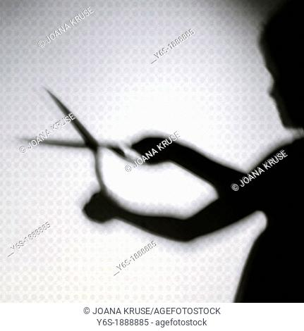 shadow of a girl who is holding scissors