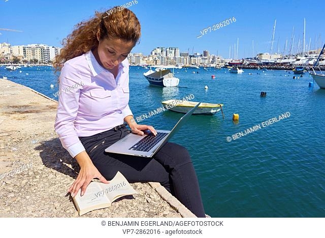 woman working with notebook computer and book next to sea in holiday destination Malta