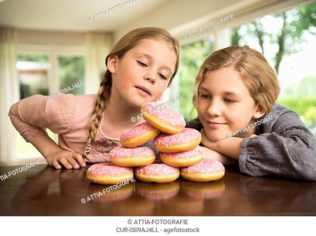Two sisters gazing at stack of with doughnut holes on kitchen counter