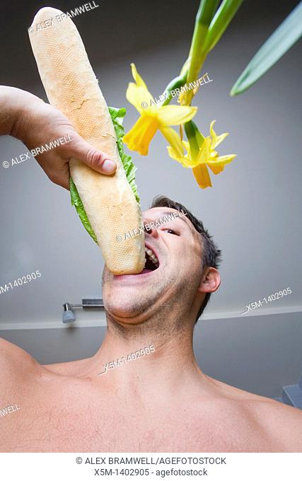Man eating a large baguette in his kitchen