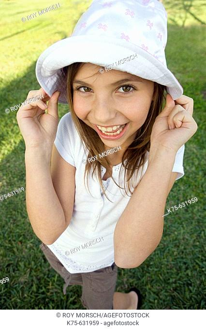 Smiling girl with hands pulling on her hat