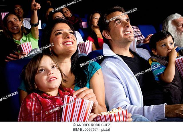 Hispanic family watching film in movie theater