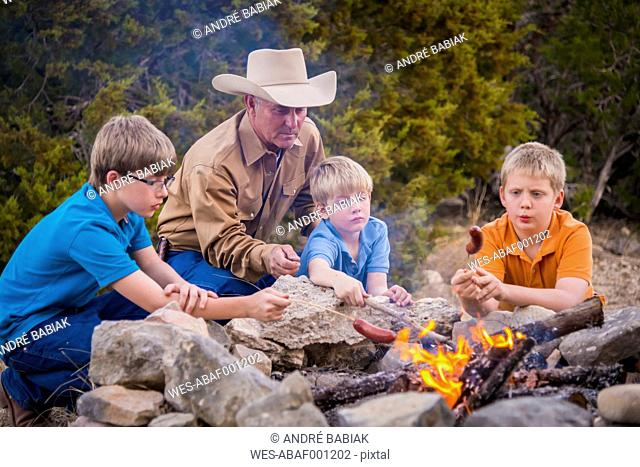 USA, Texas, Father and sons roasting sausages over camp fire