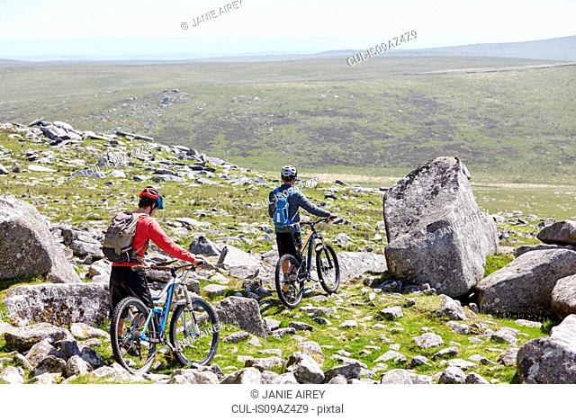 Rear view of cyclists walking bicycles down rocky hillside