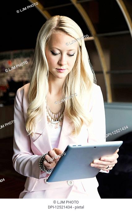A beautiful young millennial business woman with long blond hair in the workplace using technology; Sherwood Park, Alberta, Canada