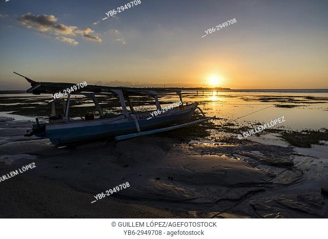 A wooden boat moored during sunset time in Gili Air, Gili Islands, Indonesia
