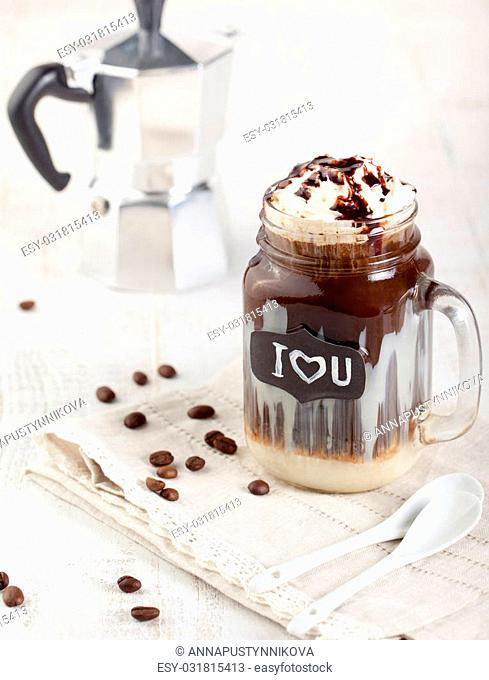 Iced coffee, frapuccino with whipped cream and chocolate syrup in a glass jar on a white wooden background