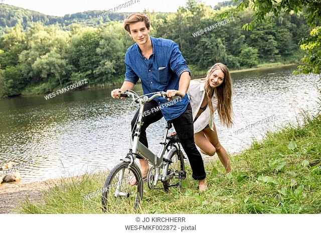Young couple with bicycle at lakeside