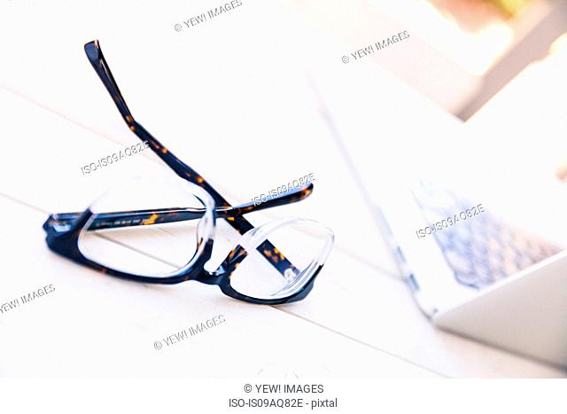 Spectacles and laptop on porch table