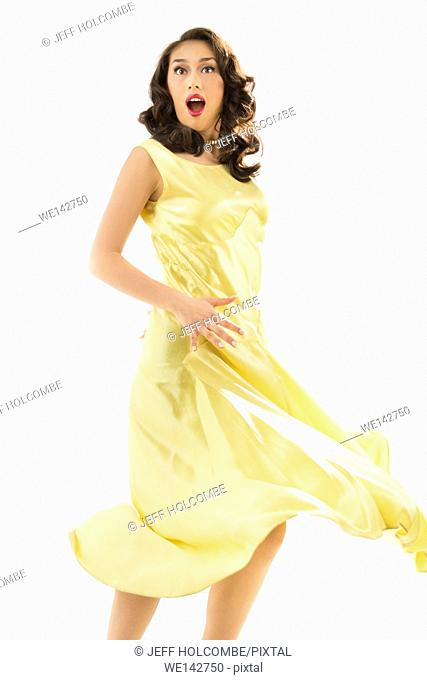 Surprised young woman in vintage yellow dress, nearly full length with dress swirling