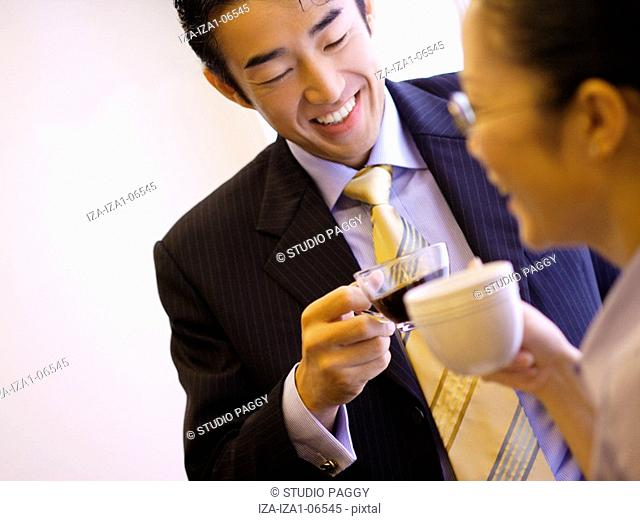 Close-up of a businessman and a businesswoman drinking tea and smiling