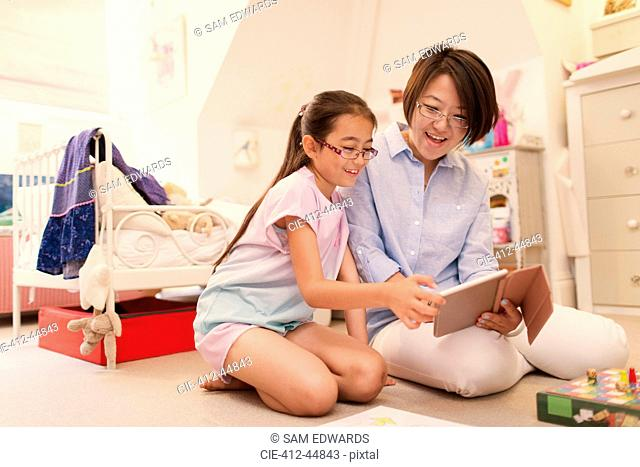 Mother and daughter using digital tablet on living room floor