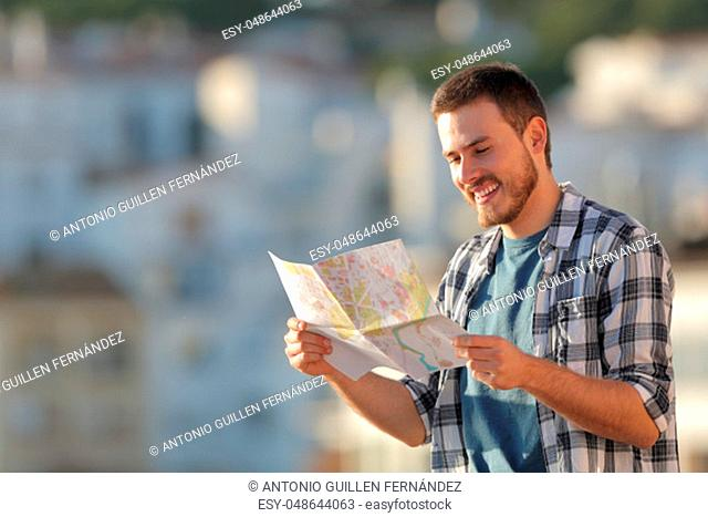 Happy tourist checking paper map in a town on vacation