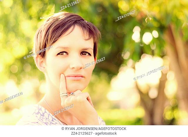 Aspirational shot of a woman with short brown hair looking out on a rural setting with visionary focus. Green ideas