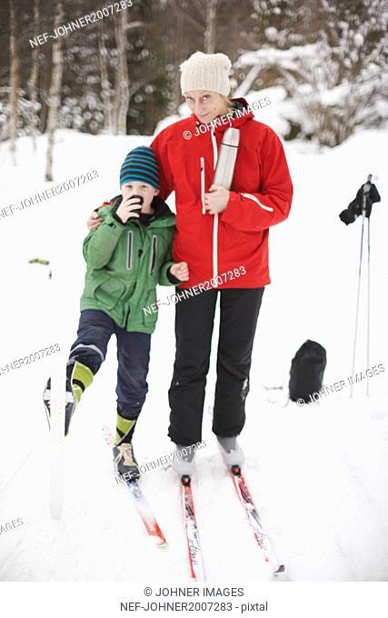 Boy having hot drink in forest