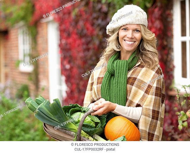 Smiling woman with seasonal vegetables