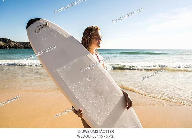 Teenage girl holding surfboard at the sea
