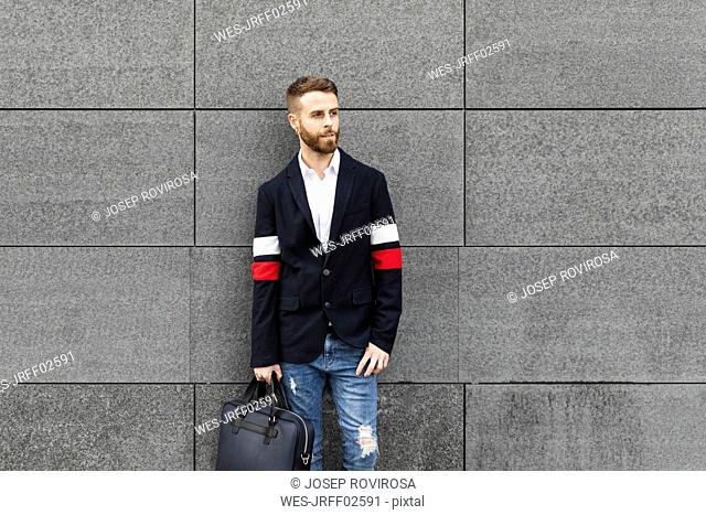 Stylish businessman standing in front of grey wall looking around