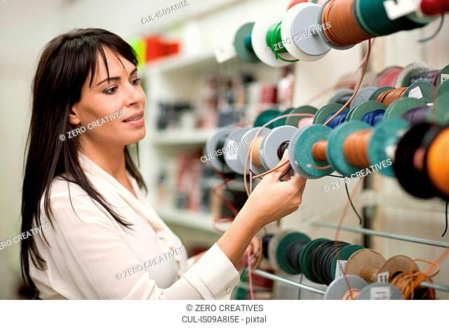 Woman looking at spools of thread in store