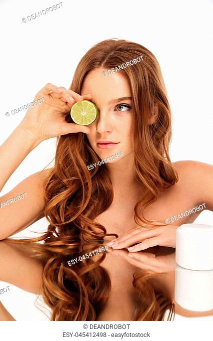 Vertical Beauty portrait of ginger woman with long hair sitting by the mirror table with body cream and citrus over grey background