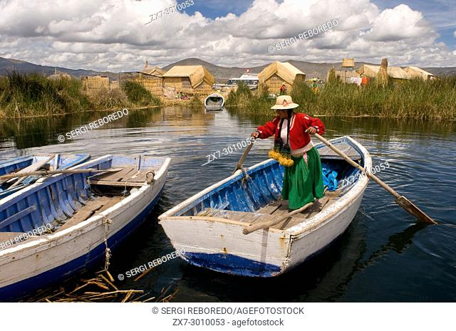 Uros Island, Lake Titicaca, peru, South America. A woman dressed in traditional regional dresses sails her boat between the Uros Islands