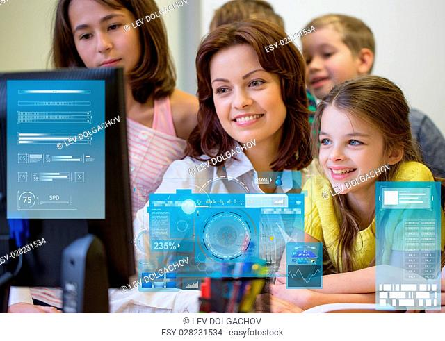 education, elementary school, learning, technology and people concept - group of kids with teacher looking to computer monitor in classroom over virtual screens...