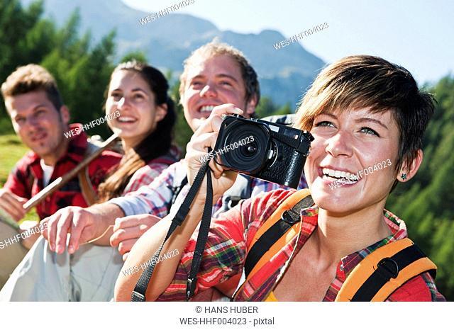 Austria, Salzburg County, Men and women sitting in alpine meadow, woman holding camera