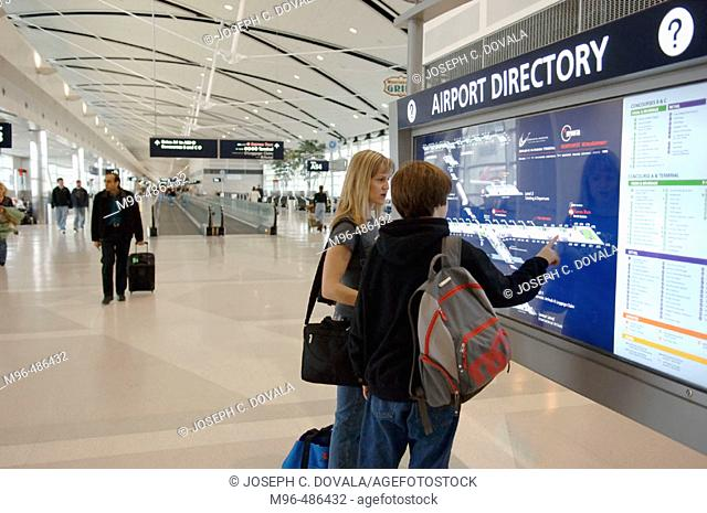 Woman and boy check airport directory in Detroit airport. Michigan, USA