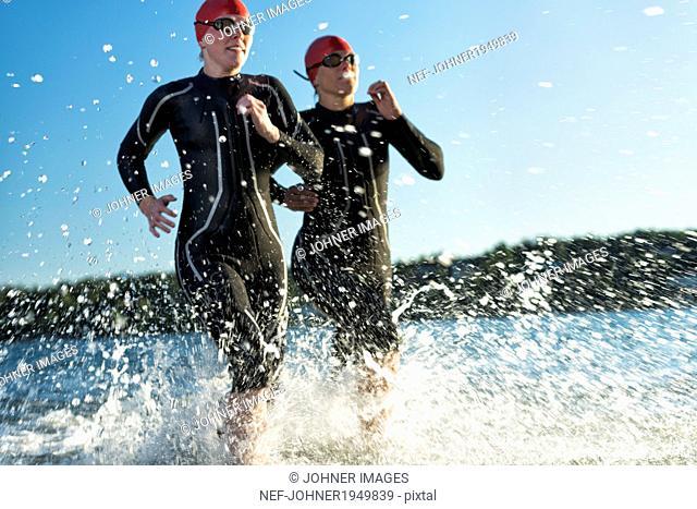 Woman in wetsuit running in sea, Sweden