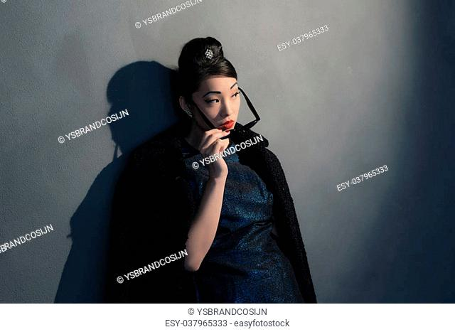 Stylish wealthy asian woman in retro 40s fashion with sunglasses. Looking over sunglasses
