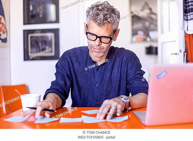 Mature man with notepads and laptop on table at home
