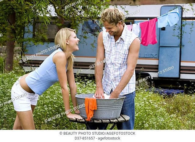 Couple having fun doing the washing outdoors