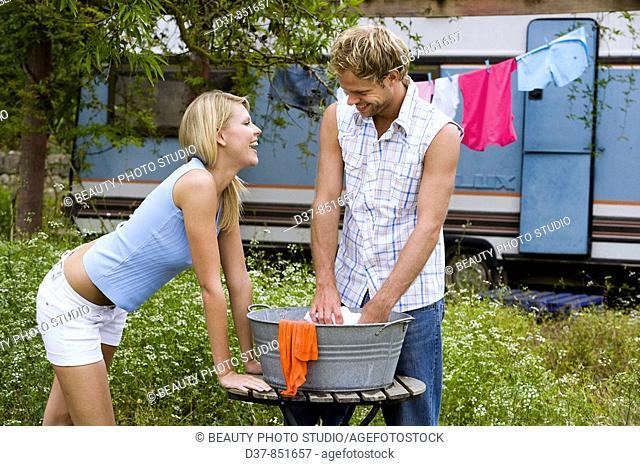 Couple having fun doing the washing outdoors