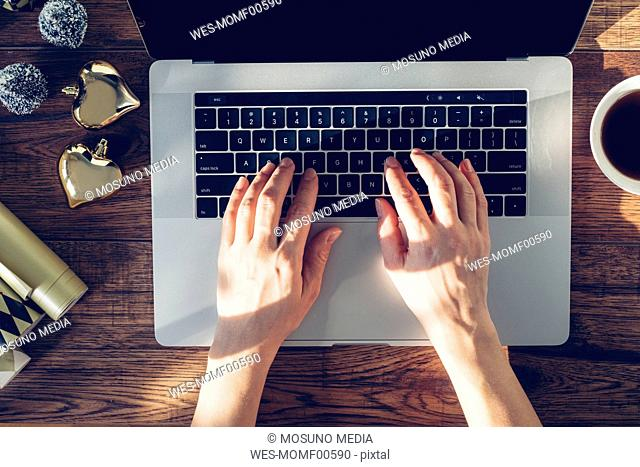 Woman's hands typing on laptop, top view