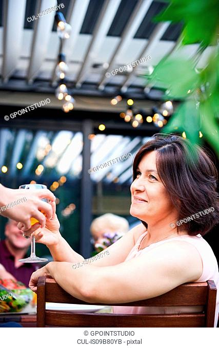 Mature woman getting handed wine at family lunch on patio table