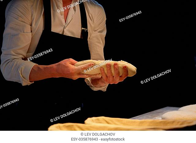 food cooking, baking and people concept - chef or baker putting yeast bread dough into baskets for rising at bakery kitchen