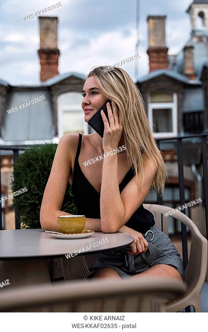 Smiling blond woman on the phone sitting on roof terrace with cup of coffee