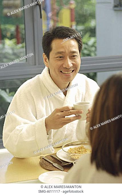 Couple facing each other, holding cups of coffee, man smiling