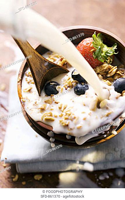 Pouring milk onto berry muesli in a cereal bowl