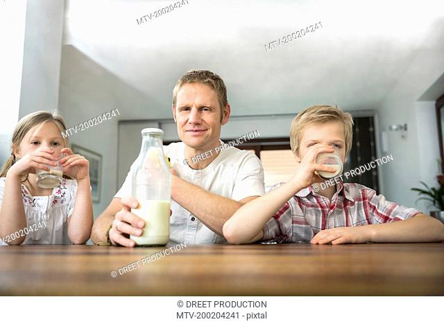 Father and his children drinking milk