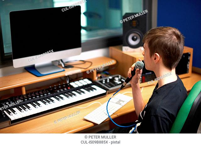 Young male college student talking into microphone in recording studio