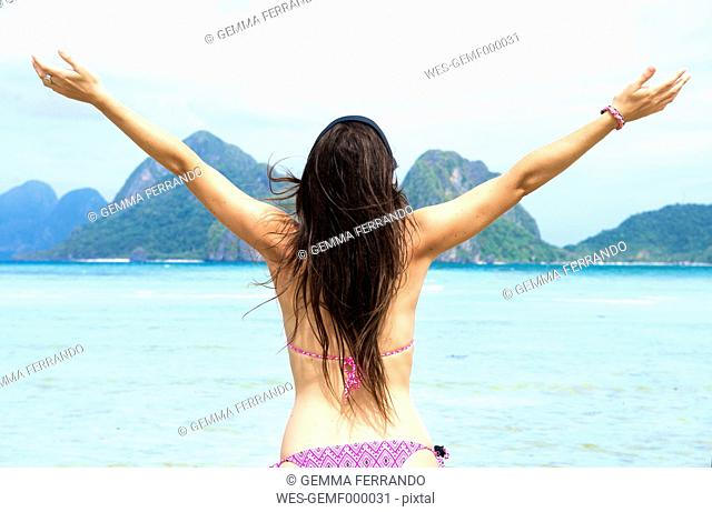 Philippines,Palawan, El Nido, woman with outstretched arms at Las Cabanas beach