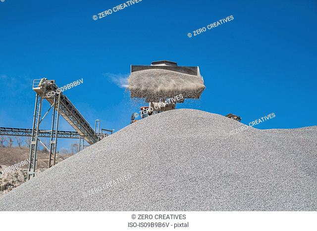 Heavy machinery at quarry, pouring aggregate onto pile