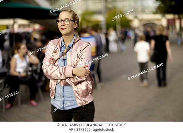 Portrait of a woman with crossed arms at pedestrian area, Alexanderplatz, Berlin, Germany