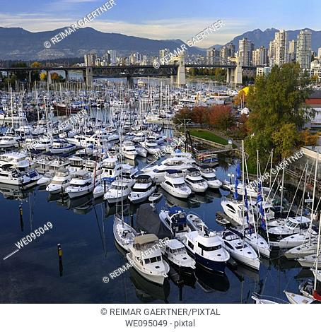 Boats moored at Granville Island Boat Yard and Burrard Marina with bridge and Coastal mountains Vancouver